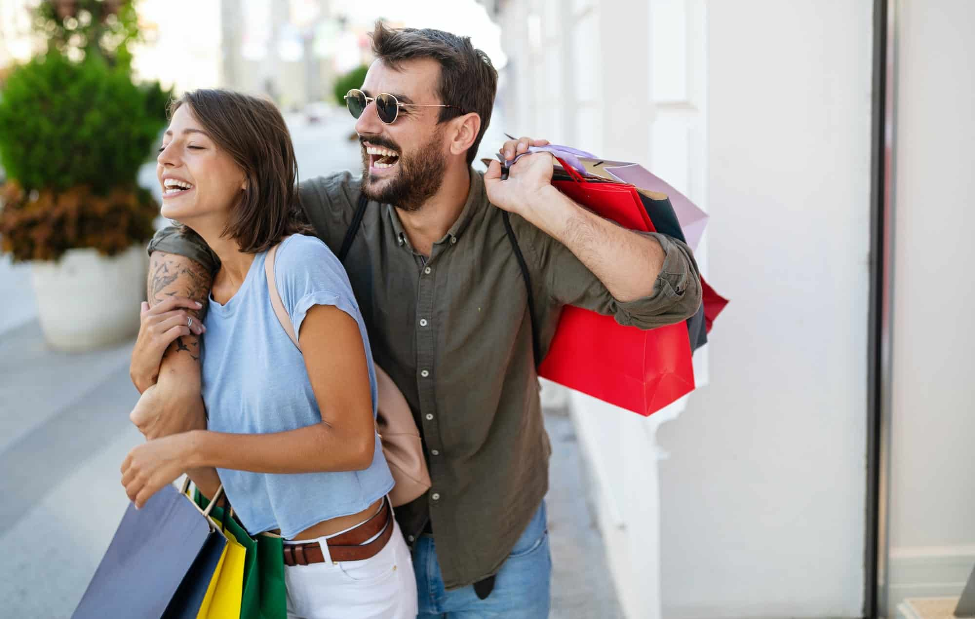 Young attractive happy couple with shopping bags outdoors